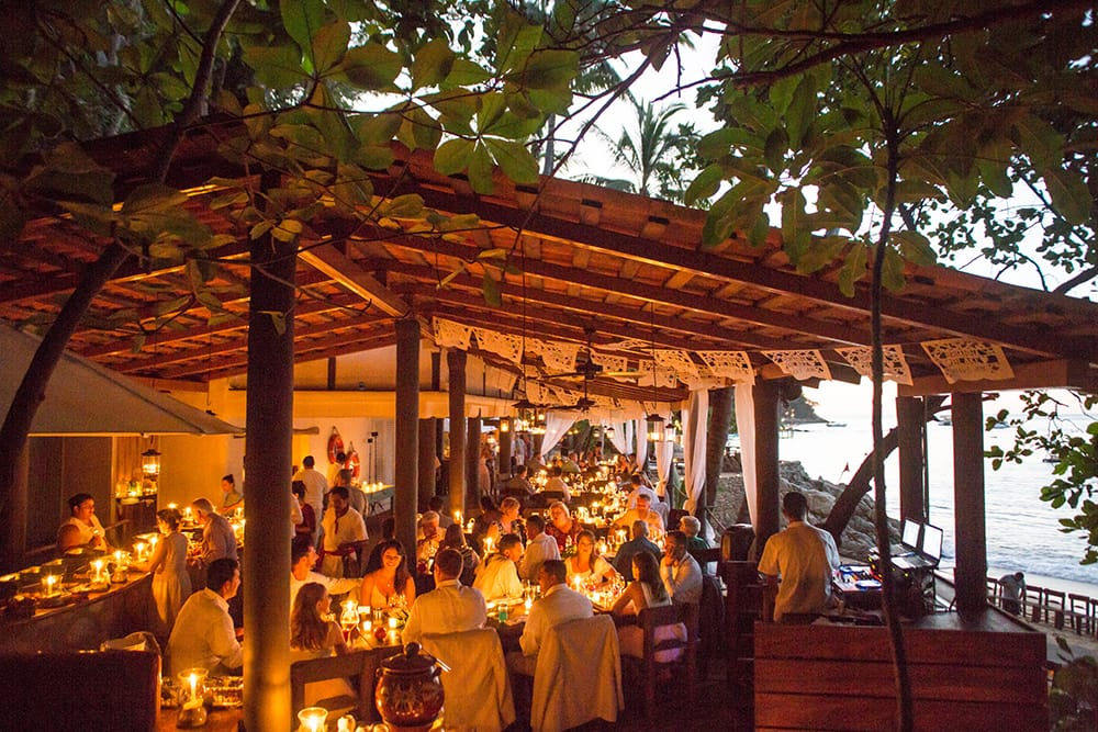 Guests eating dinner at sunset reception with candle accents at private beach wedding venue in Mexico