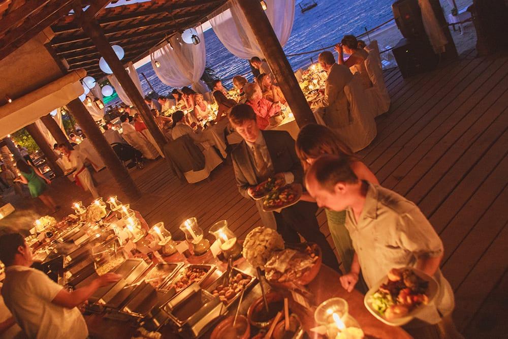 Sunset destination wedding ceremony with candlelit buffet
