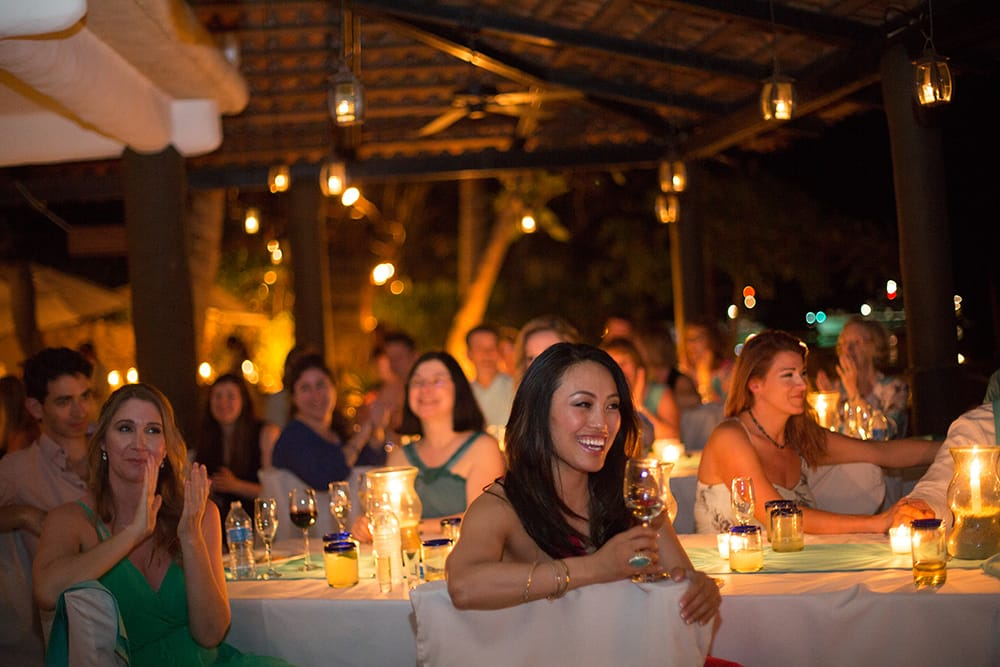 Guests enjoying speeches during dinner at beach destination wedding reception in Mexico