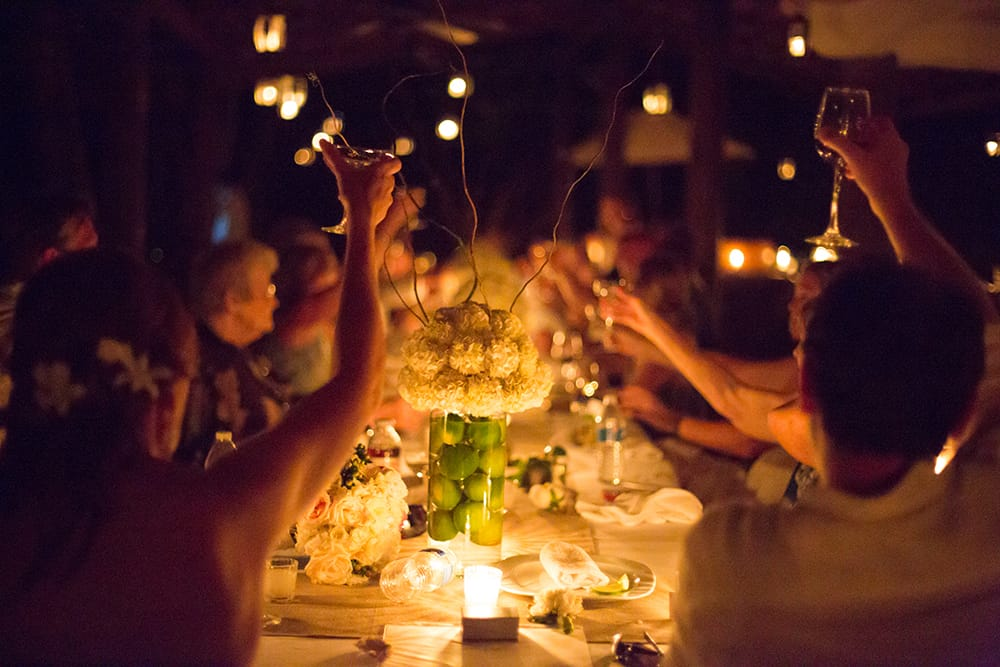 Toast to the bride and groom at evening candlelit beach reception at destination wedding