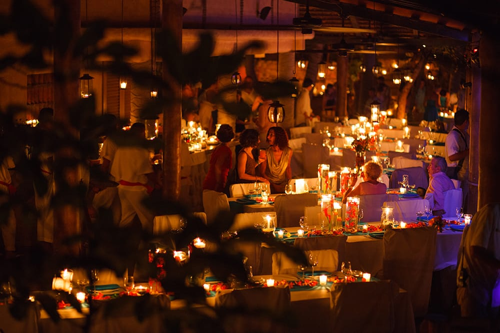 Guests enjoying the bar service in the candlelit pavilion at Adventure Weddings private beach venue for destination wedding reception