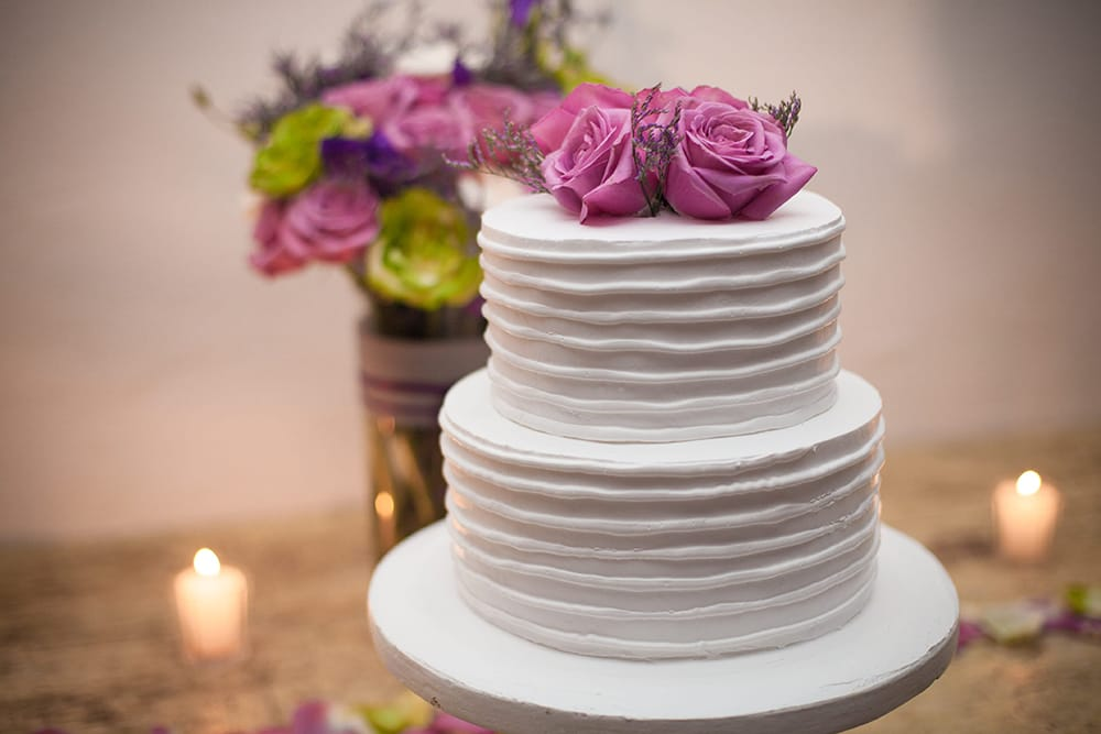 Classic buttercream wedding cake with fresh flower cake topper by Adventure Weddings