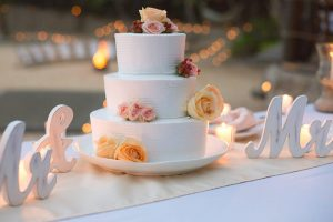 Classic white three tiered wedding cake with fresh flower accents by Adventure Weddings