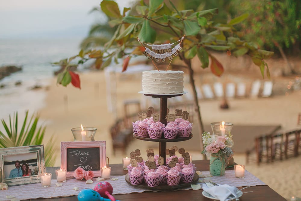 Cutting cake and pink cupcakes for outdoor destination wedding by Adventure Weddings