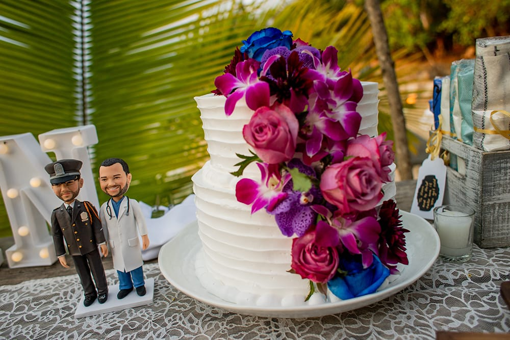 Two tiered buttercream wedding cake with fresh tropical flowers by Adventure Weddings