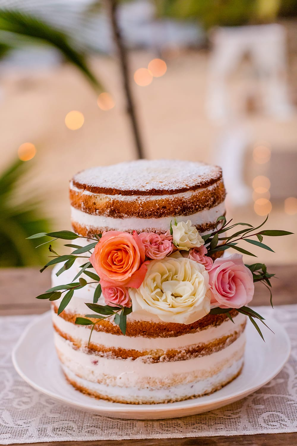 Two tiered naked wedding cake with fresh flowers by Adventure Weddings
