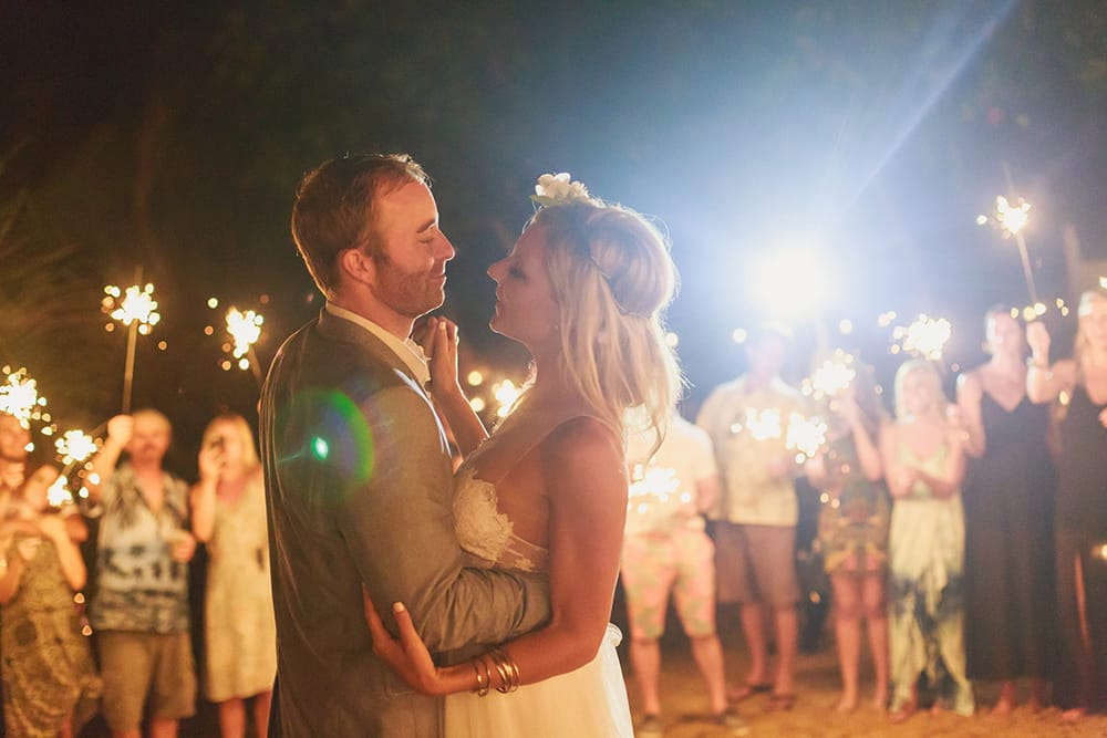 Couples first dance at destination wedding lit by guests with sparklers during beach reception
