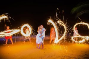 Wedding guests spelling 'love' with sparklers at casual destination wedding in Mexico