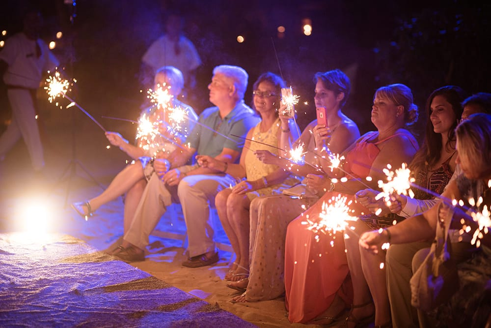 Wedding guests holding sparklers at destination wedding coordinated by Adventure Photos