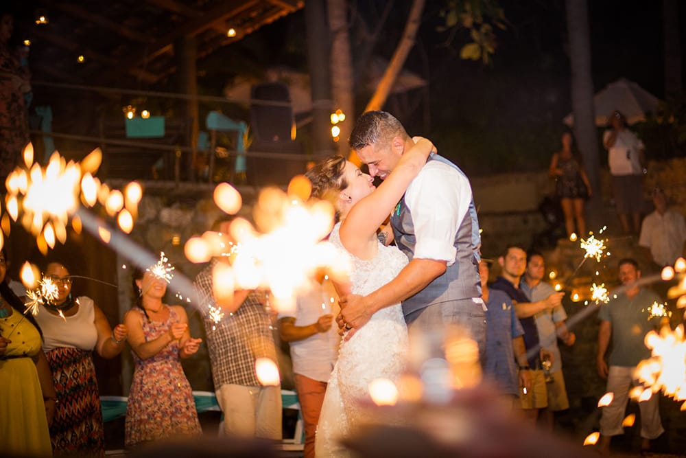 Bride and groom sharing first dance at destination wedding surrounded by sparklers