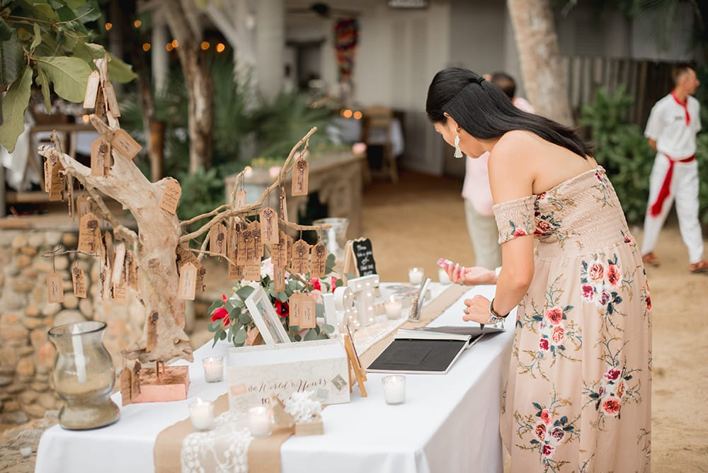 Guestbook signing table with vintage keys hanging from a tree as favours and place cards for guests at a destination wedding in Mexico
