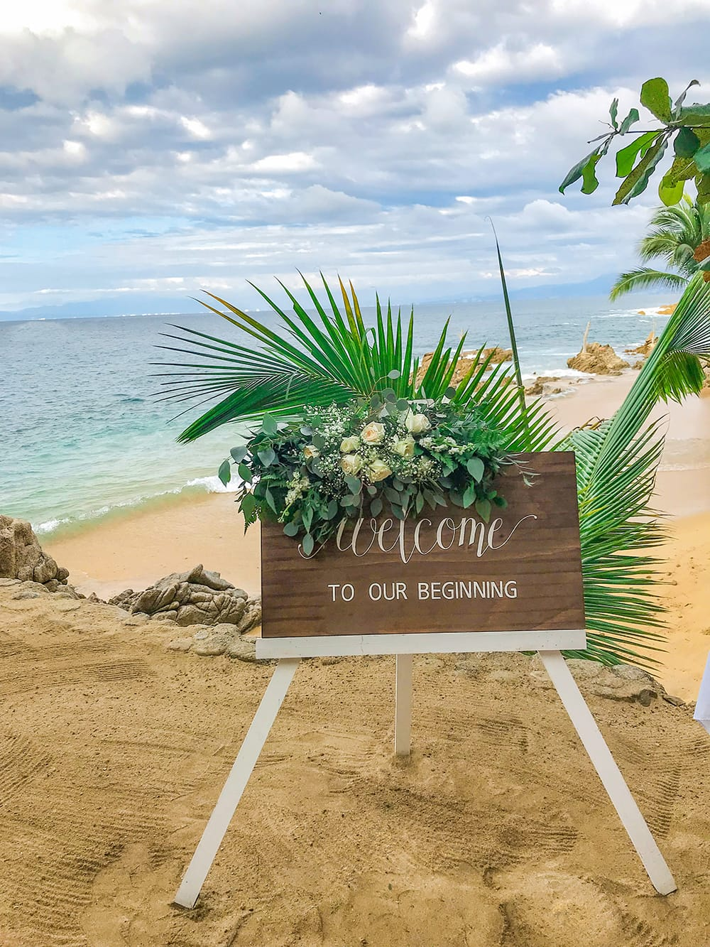 Wooden welcome to our wedding sign with floral accent for beach wedding ceremony in Mexico