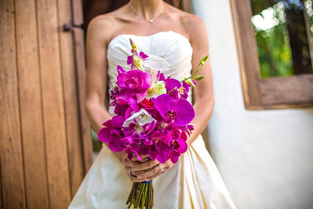 Tropical wedding bouquet of fuchsia flowers by Adventure Weddings' destination wedding florist