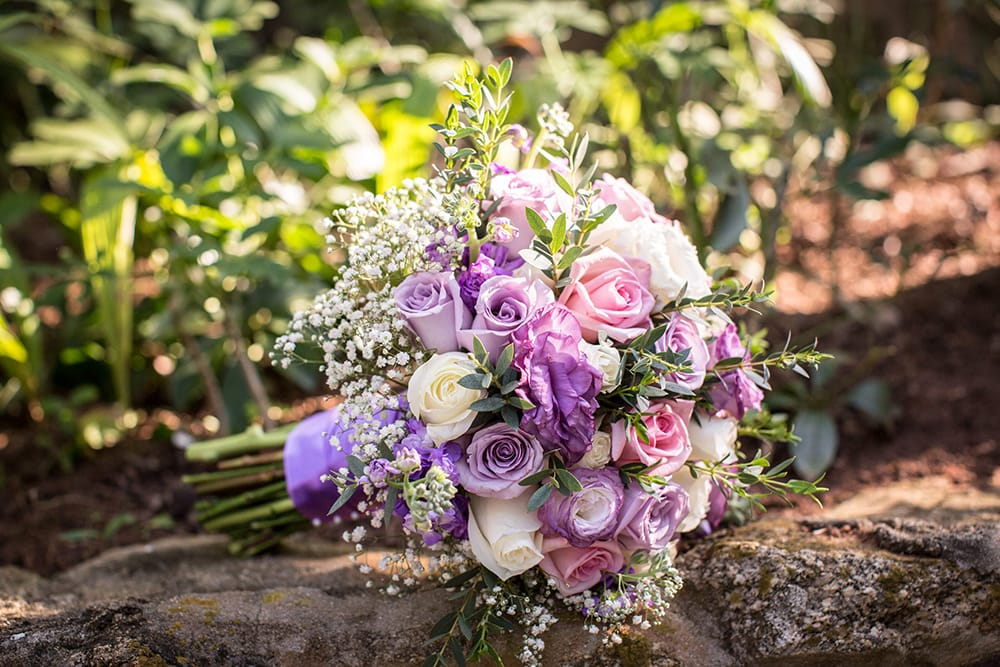 Pink and purple traditional wedding bouquet with baby's breath by Adventure Weddings' destination wedding florist