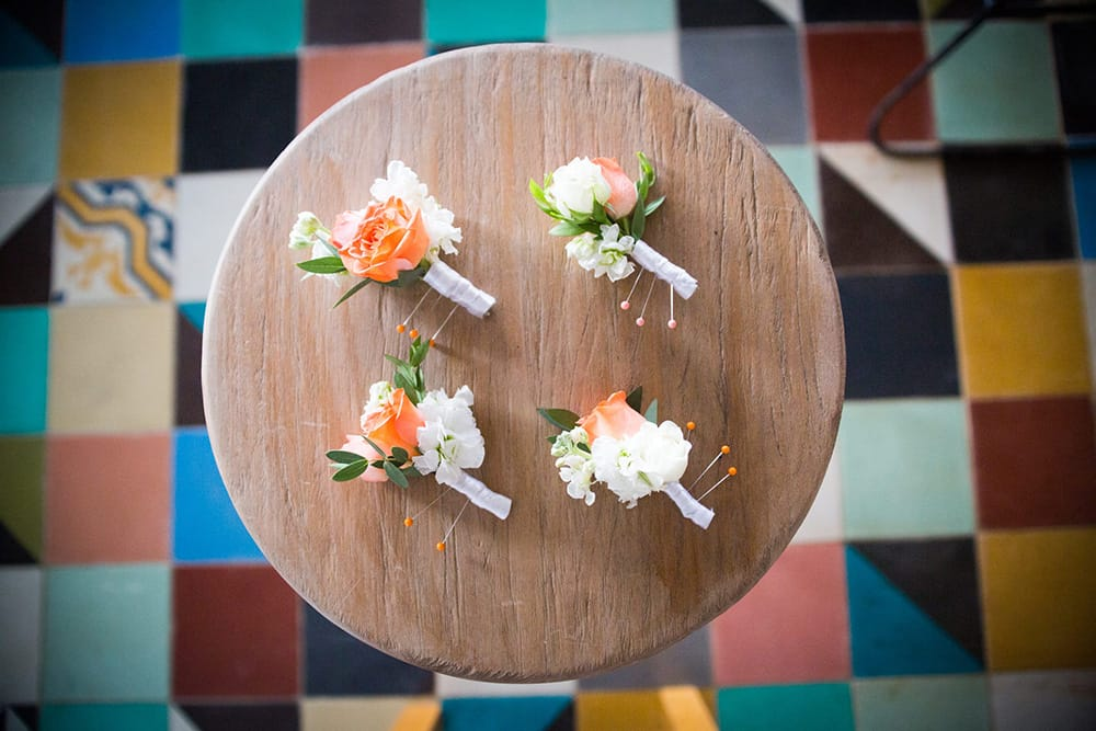 Colourful coral boutonnieres for bridal party by Adventure Weddings' destination wedding florist