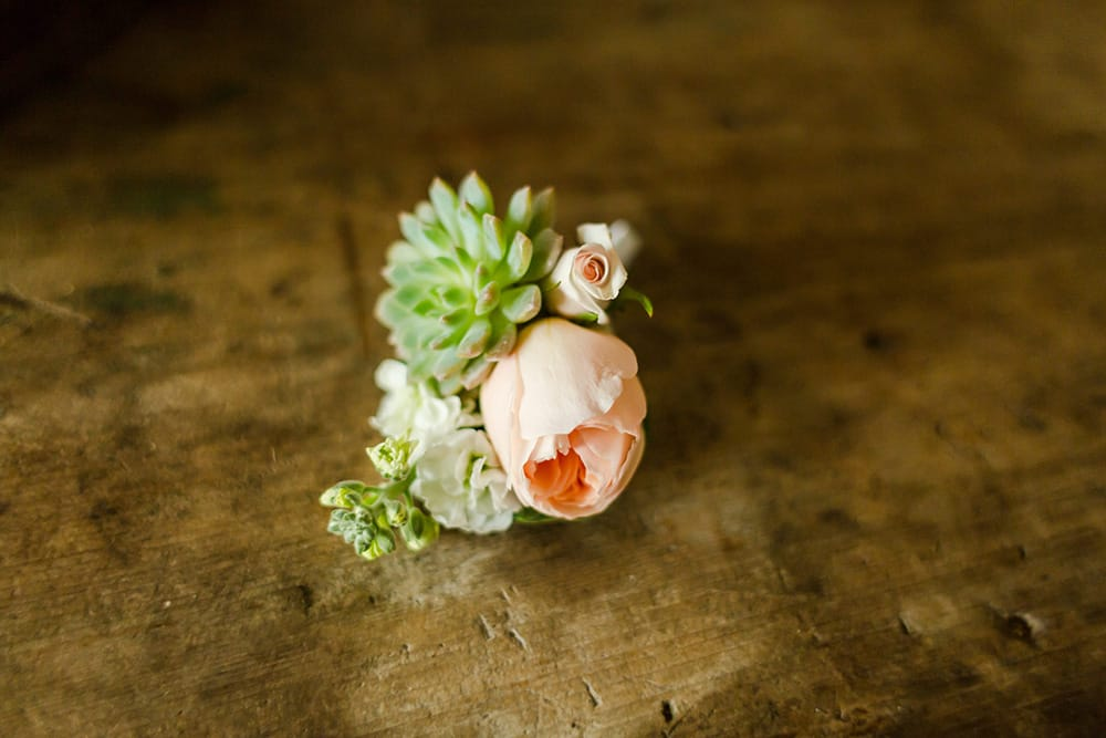 Peach rose and succulent boutonniere by Adventure Weddings' destination wedding florist