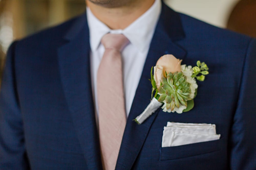 Simple peach boutonniere for groom by Adventure Weddings' destination wedding florist