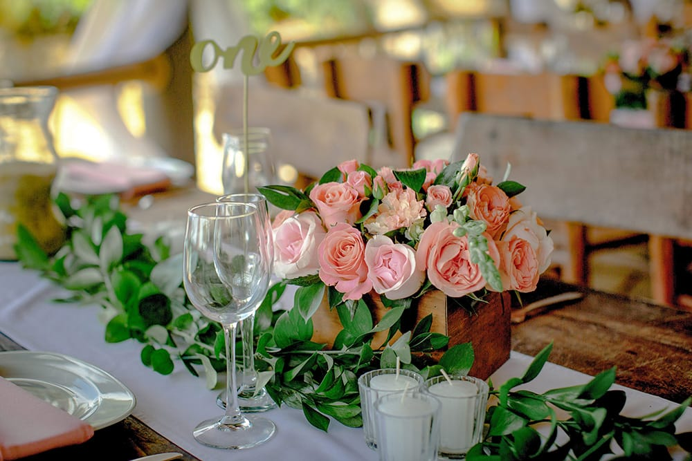 Pink rose centerpieces for harvest tables by Adventure Weddings' destination wedding florist