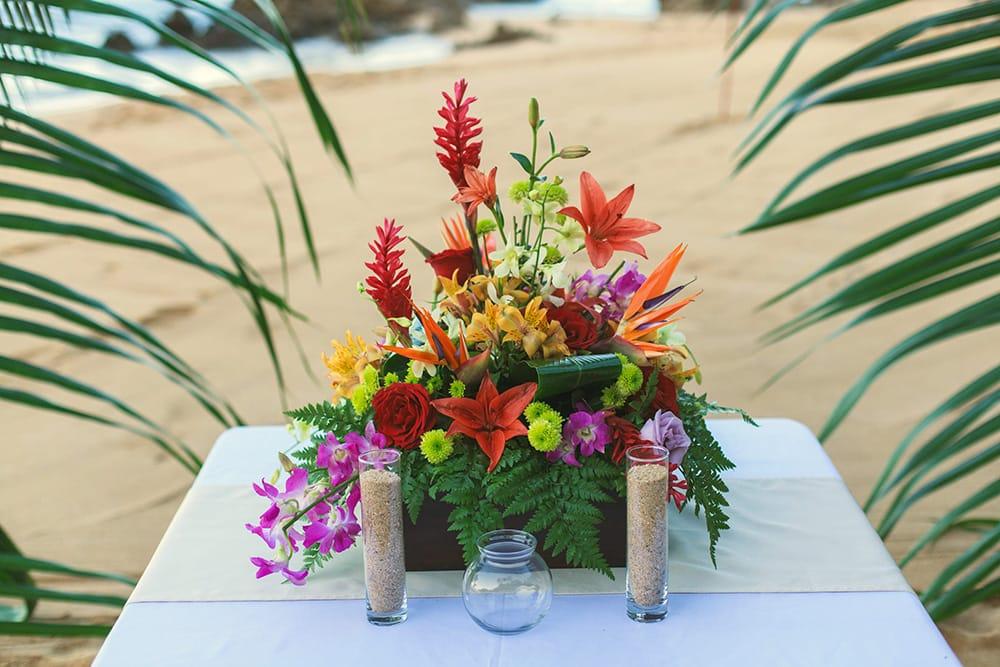 Tropical floral arrangement for beach reception by Adventure Weddings' destination wedding florist
