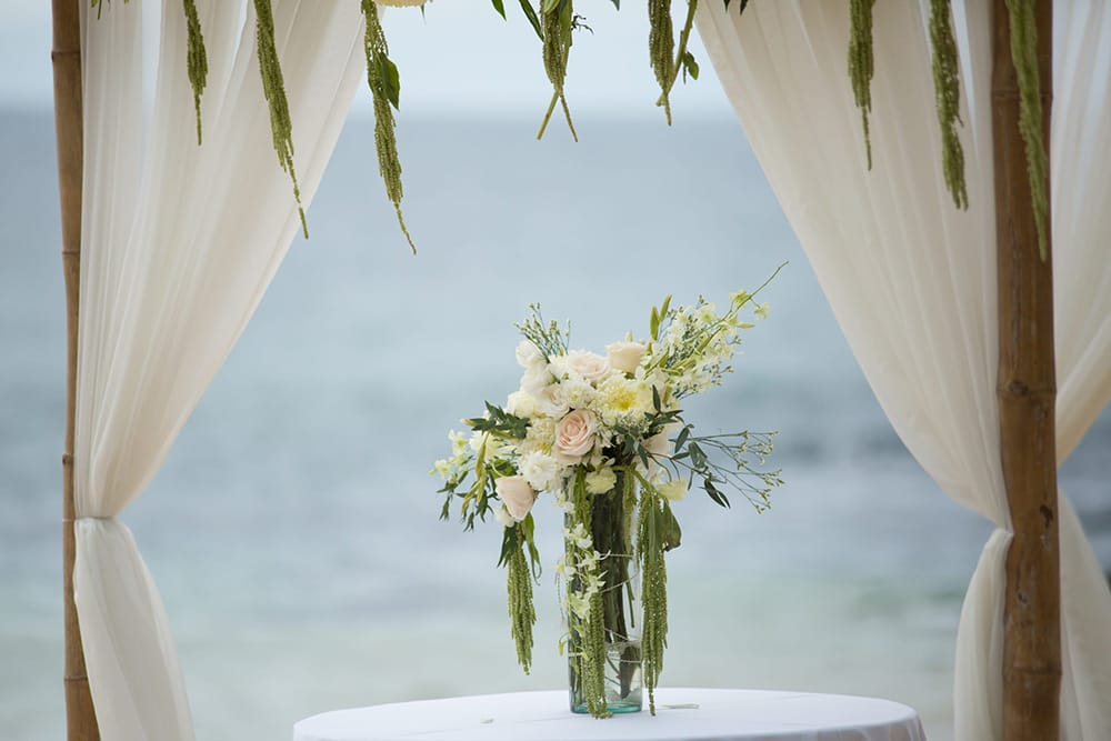 Floral arrangement for signing table at beach wedding ceremony in a tall vase by Adventure Weddings' destination wedding florist