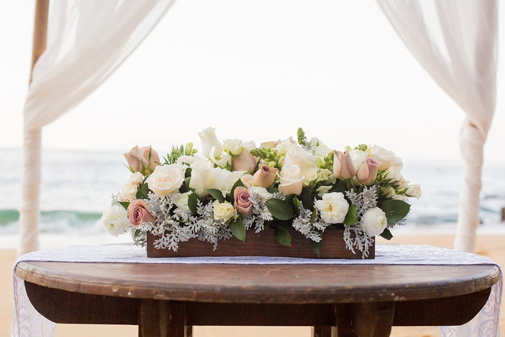 Rose floral arrangement for signing table at beach ceremony by Adventure Weddings' destination wedding florist