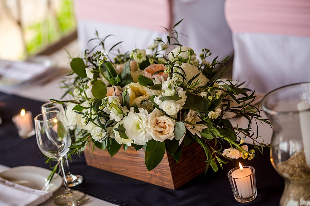Stunning wedding centerpiece of toffee, cream and white roses at destination wedding reception by Adventure Weddings' florist