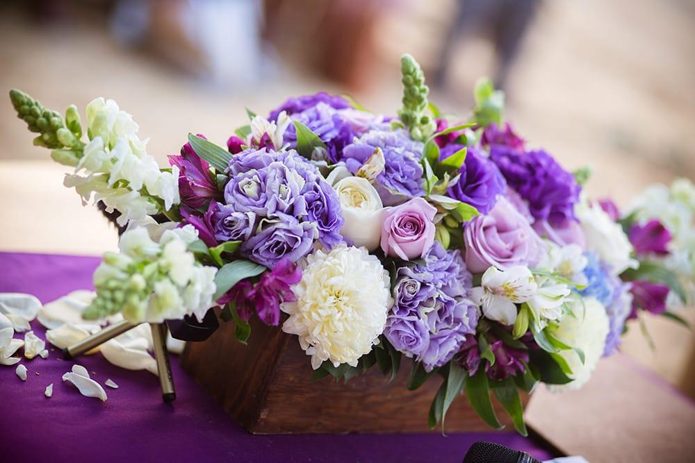 Purple floral arrangement for centerpieces at destination wedding reception by Adventure Weddings' florist