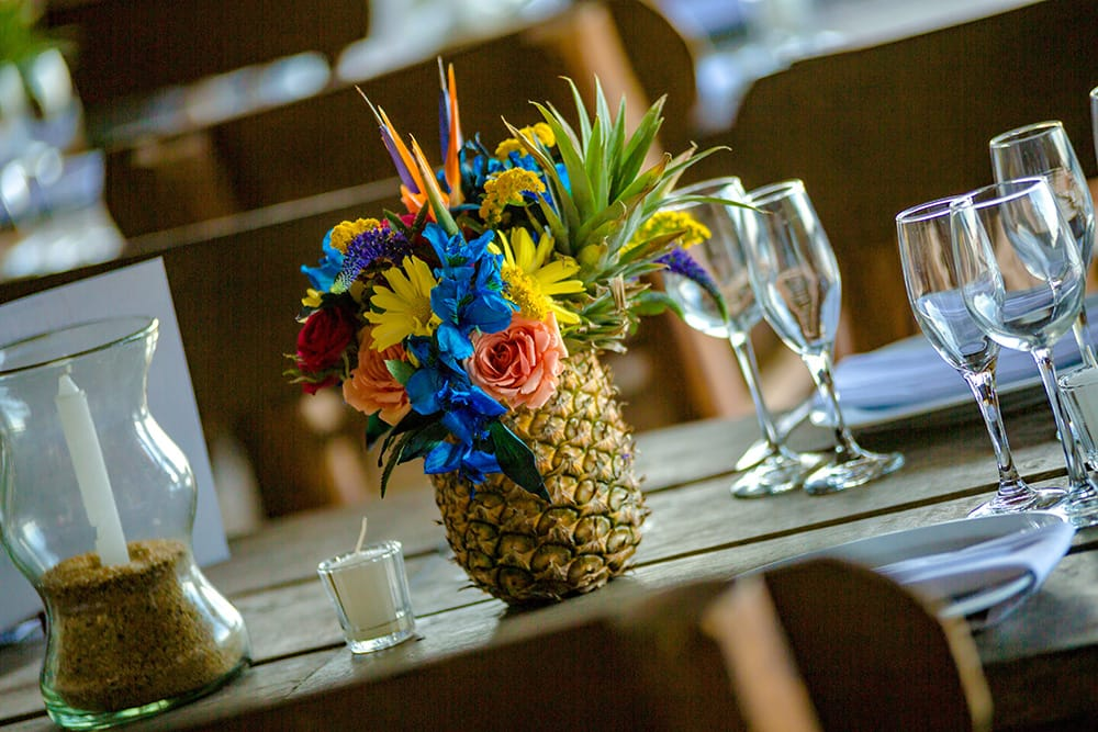 Tropical floral centerpiece for destination wedding arranged in a pineapple by Adventure Weddings' florist