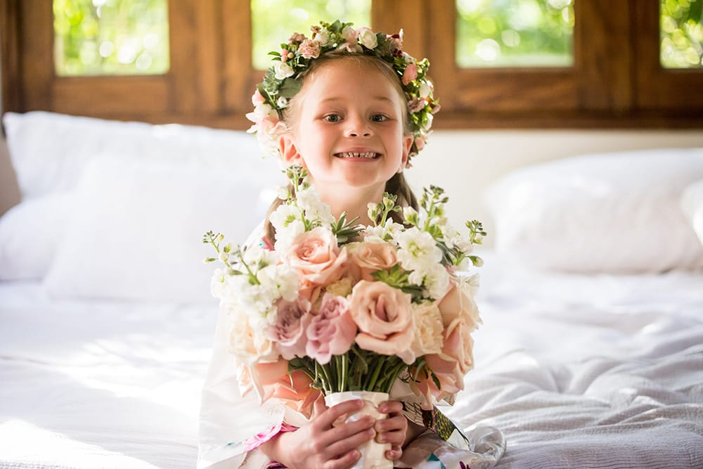 Flower girl holding bouquet of soft pink roses and wearing a floral crown designed by Adventure Weddings' florist