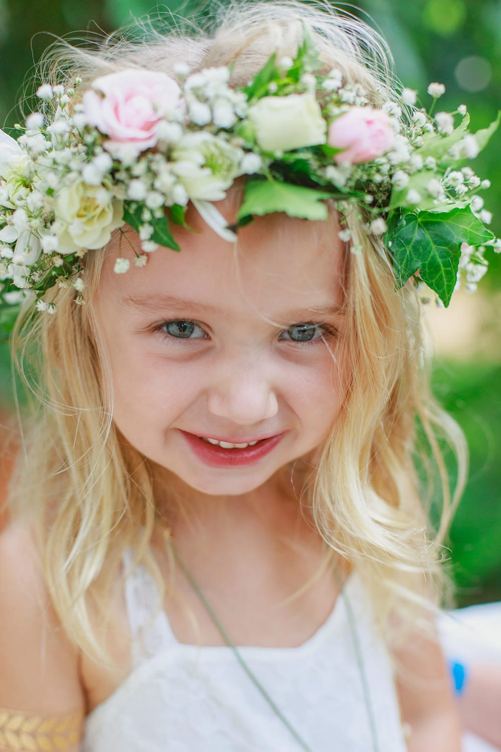 Adorable flower girl with spray rose flower crown for beach wedding ceremony designed by Adventure Weddings' florist