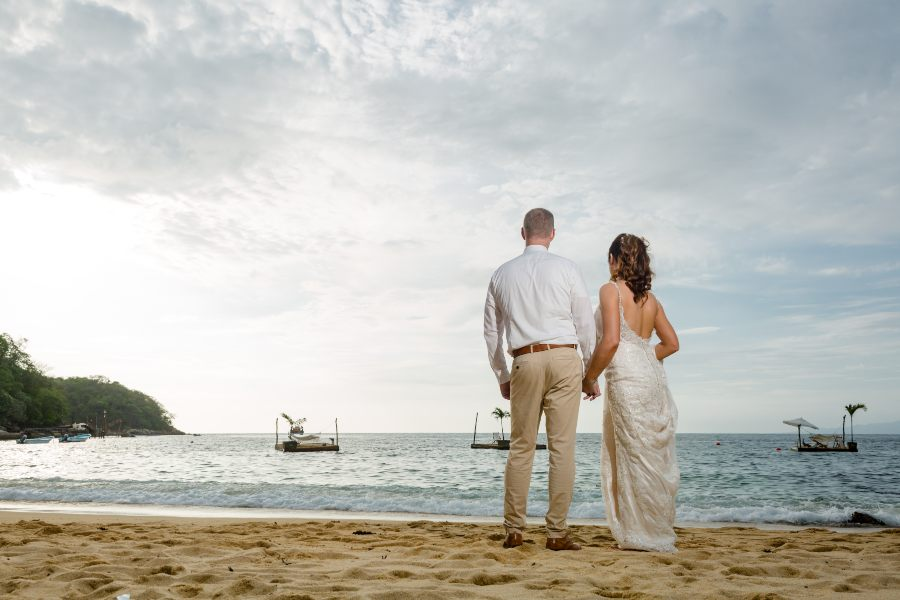 Couple Looking at Stunning Sunset During Barefoot Wedding at Las Caletas